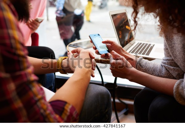 Closely image of woman is making an on-line purchase via cell telephone, while is sitting with friends in hipster cafe interior. Young female is reading information on web page via her mobile phone