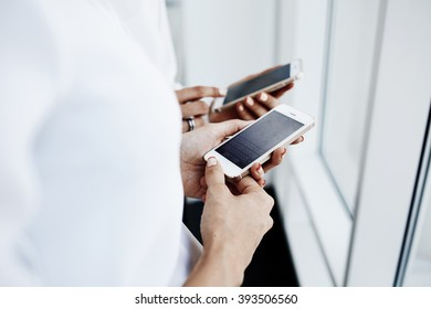 Closely image of a woman`a hands is holding cell telephone, while her friend is searching information in network. Two business female are reading finance news on mobile phones during work break