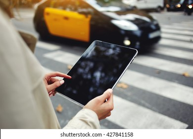 Closely image of woman`s hand is holding portable digital tablet with copy space screen for your advertising text message or promotional content, while is standing on the street near road pedestrian