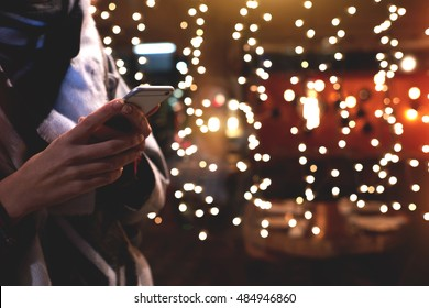 Closely image of young hipster girl is using her smart mobile phone, while is standing on the street against christmas garlands lights. Woman chatting with friends in social network via cell telephone