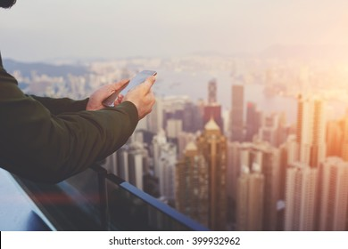 Closely of man successful broker is using mobile phone,while is standing on building roof against view of New York city with tall skyscrapers. Hipster guy is connecting to internet via cell telephone