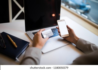 Closely woman business owner makes online purchase via smartphone using debit credit card after work on laptop computer sitting in office interior. Female online shopping store via cell telephone