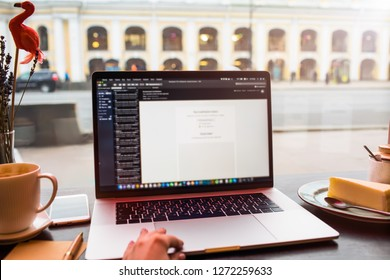 Closely woman writer touching trackpad of modern laptop computer with blurred web sites on the screen. Open netbook on coffee shop table against window with street view