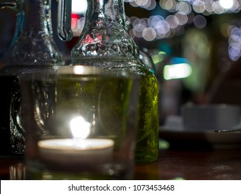 A closely-taken table in a restaurant with a candle and a bottle of vegetable oil green with a blurred background. Romantic setting.