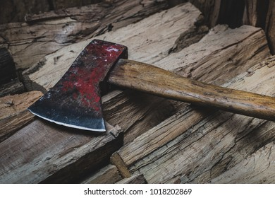 Closep of hatchet axe lying on a pile of split wood logs used for fire. Concept of making logs portrayed in natural colors- Axe viewed from the top side with a shiny sharp blade.