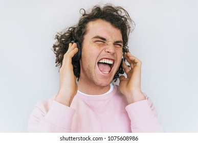 Closep shot of freedom handsome stylish young male with curly hair wearing pink clothes, singing and listening favorite music on headphones, isolated on white studio wall. Copy space for advertisement