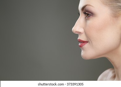 Closer glance. Cropped closeup profile of a gorgeous mature woman smiling copyspace on the side on the grey background