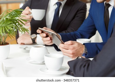 Closer look. Cropped closeup of a businessman showing his colleagues something on his digital tablet at a business lunch