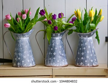 A closer shot of the milk tins full of tulips.