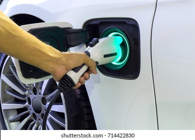 Closes up Human hand is holding Electric Car Charging connect to Electric car with green light display full battery.