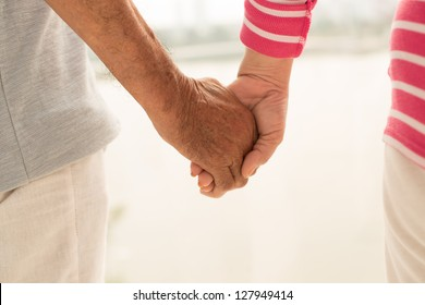 Close-shot of seniors holding hands expressing love and support