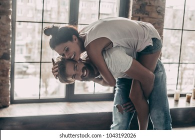 Closest friends and lovers. Young passionate couple having fun together and looking happy while handsome young man carrying his girlfriend on shoulders