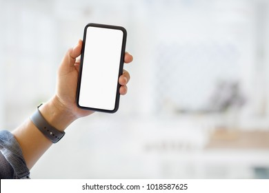 Closes-up shot of man hand holding blank screen smartphone over blurred background.