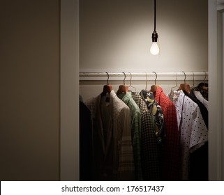 Closet with Clothes and Bare Lightbulb