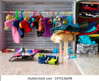 Closet with colorful clothes. Clothes on hangers, on shelves, in a box, on a furry stool and on the floor. Colorful shoes on the floor. Messy dollhouse.