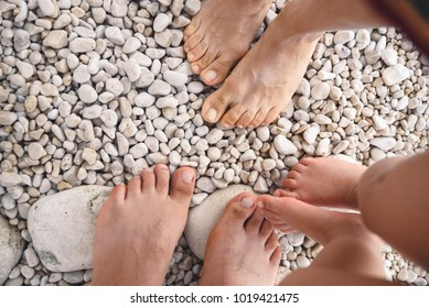 closeuo of feet of family standing on beach stones