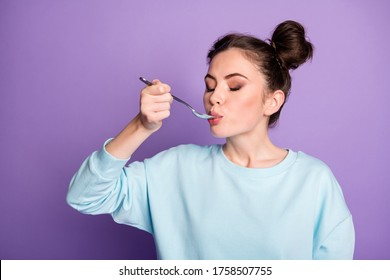 Close-uo portrait of her she nice attractive charming dreamy girl licking spoon eating delicious meal dish dinner isolated on violet purple lilac bright vivid shine vibrant color background