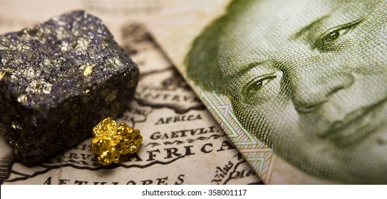 Close-up of a 1 yuan Chinese banknote (figuring Mao) and a gold nugget / rare earth metal on top of an antique map of Africa