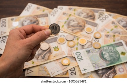 close-up of a 1 zloty coin held in a hand on the background of various banknotes Polish money, zloty, PLN