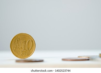 Closeup of 10 cent dollar coin standing on wooden table with white background.