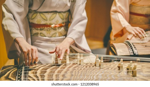 A close-up of 2 women wearing kimono are playing Koto - a traditional Japanese stringed musical instrument