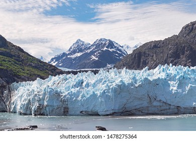 closeup of the 350 foot high margerie glacier in glacier bay park in alaska with mount fairweather in canada in the background