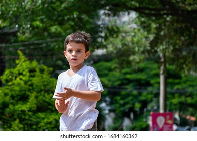 Close-up of a 6 year old child in a public square and touching his hands.