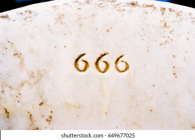 Closeup of 666 engraved in headstone