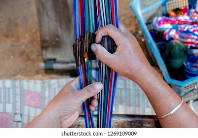 Closeup from above of female nepalese weaver creating a colorful belt