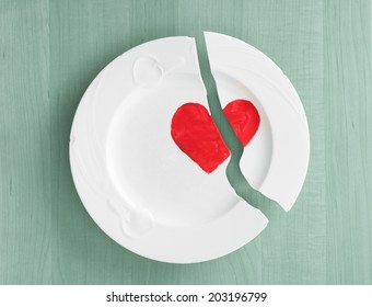 Closeup above view of broken white ceramic china plate dish with a red heart painted on it, on teal blue wood board background.  Concept or metaphor for divorce, relationships, friendships,