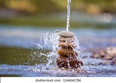 Close-up abstract image of water pouring down on rough natural brown uneven different sizes and forms stones balanced like pyramid pile landmark on blurred blue-green misty copy space background.