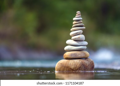 Close-up abstract image of wet rough natural brown uneven different sizes and forms stones balanced like pyramid pile landmark in shallow water on blurred blue-green misty copy space background.