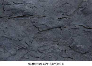 Closeup abstract shale texture background with lines and cracks and alternating layers of orange and blue stratification.