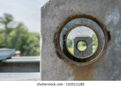 Close-up, abstract view of a cobweb seen inside a metal hole, used on steelwork for bridge construction on a border crossing in East and West Germany. Creating a gunsight effect to another hole.