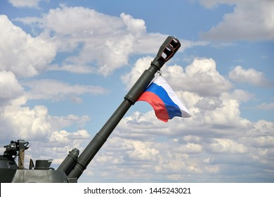 A closeup of an Acacia 2S3 cannon with a Russian flag. Soviet 152-mm divisional self-propelled howitzer against the sky.