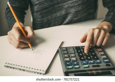 Closeup of Accountant Using Calculator and Writing