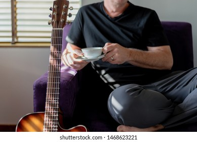 Closeup of acoustic guitar and man relaxing with cup of coffee on purple couch