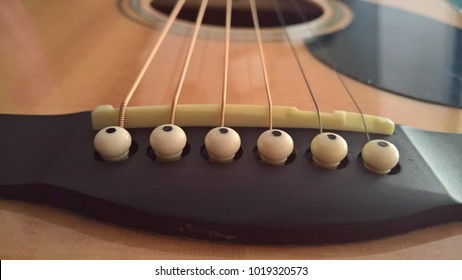 closeup of acoustic guitar strings and mount