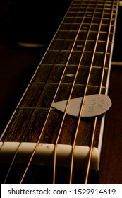 Closeup of acoustic guitar strings with plectrum