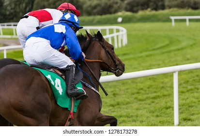 Close-up action on two race horses and jockeys galloping for position.