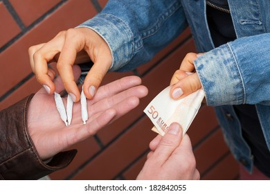A closeup of addicts exchanging joints for banknotes