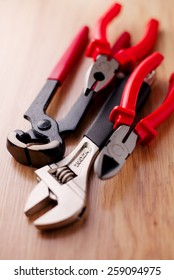 Closeup adjustable wrench, pliers, claw hammer and pliers on the wooden background