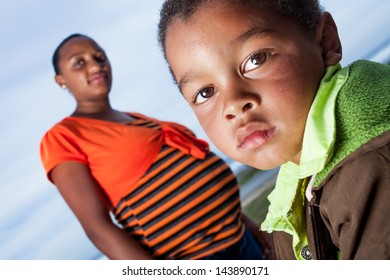 a close-up of an adorable african boy dressed in a warm brown and green jacket with his young pregnant mother  wearing an orange striped shirt standing behind him protectively in the outdoors