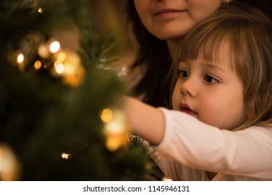 Closeup of an adorable child decorating xmas tree