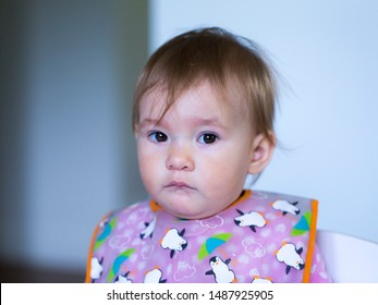 Closeup of adorable fair toddler girl wearing a bib sitting in chair staring with unhappy expression