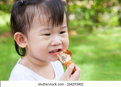 Closeup adorable little asian (thai) girl enjoy eating her lunch in the park, child eating fried chicken over blur green nature background