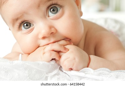 Close-up of adorable little baby face lying with hand in mouth, looking up