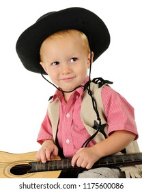 Close-up of an adorable toddler cowboy happily playing a guitar.