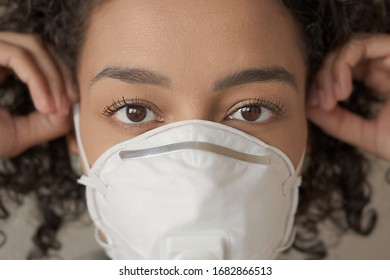 Closeup of adult african american woman putting mask on her face. Action to prevent the spread of the virus by infected people. Coronavirus or Covid-19 quarantine
