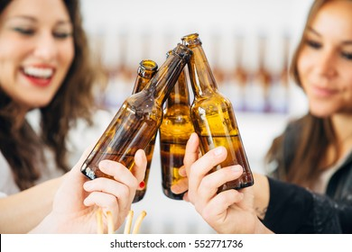 Close-up of adult cheerful women and unrecognizable men toasting with bottled beer